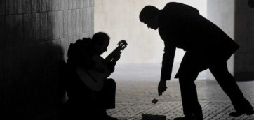 A passer-by gives some money to a street musician playing guitar in a pedestrian subway in central Kiev on March 30, 2010. AFP PHOTO/SERGEI SUPINSKY